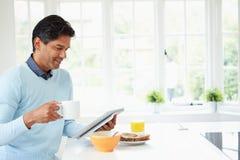 Homem indiano que usa a tabuleta de Digitas enquanto comendo o café da manhã Imagem de Stock
