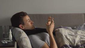 Homem insalubre na cama ao lado de suas medicamentações em sua casa que chama o telefone Vírus de sofrimento da gripe do frio e d Foto de Stock