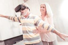 Homem interessado superior que está e que olha através dos vidros de VR fotografia de stock