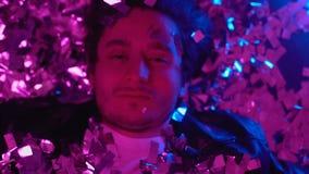 Homem intoxicado que encontra-se no assoalho coberto com os confetes, edição do abuso de drogas, vista superior vídeos de arquivo