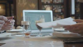 Homem irreconhecível e mulher que sentam-se na tabela no funcionamento do café O portátil, os papéis e os vidros com café estão n vídeos de arquivo