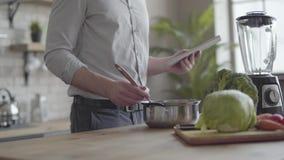 Homem irreconhecível na camisa que cozinha a sopa que verifica a receita na tabuleta na cozinha em casa Conceito de saud?vel vídeos de arquivo