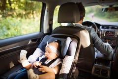 Homem irreconhecível que conduz com um bebê foto de stock royalty free