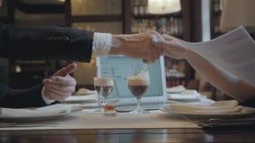 Homem irreconhec?vel e mulher que sentam-se na tabela no funcionamento do caf? O port?til, os pap?is e os vidros com caf? est?o n vídeos de arquivo