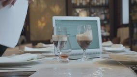Homem irreconhec?vel e mulher que sentam-se na tabela no funcionamento do caf? O port?til, os pap?is e os vidros com caf? est?o n filme