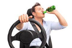 Homem irresponsável novo que conduz e que bebe uma cerveja Foto de Stock
