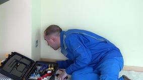 Homem irritado do eletricista com tensão do teste do indicador no soquete de parede bonde vídeos de arquivo