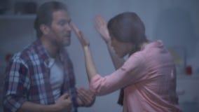 Homem irritado e mulher que discutem em casa atrás da janela chuvosa, engano video estoque
