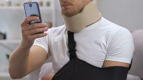 Homem irritado no estilingue cervical do colar e do braço que datilografa no telefone, problema do seguro vídeos de arquivo