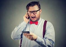 Homem irritado que discute no smartphone Fotografia de Stock Royalty Free