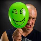 Homem irritado que esconde atrás do balão feliz Imagens de Stock