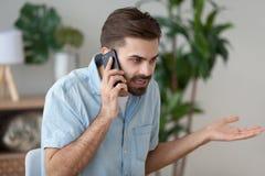 Homem irritado que fala no smartphone que resolve o problema do trabalho foto de stock