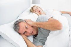 Homem irritado que obstrui suas orelhas do ruído da esposa que ressona Fotografia de Stock