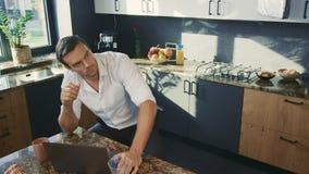 Homem irritado que senta-se na cozinha luxuosa Marido irritado que tem o conflito com esposa filme