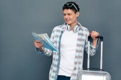 Homem isolado na posição cinzenta do conceito do turismo da parede com a bagagem que olha o mapa excitado imagem de stock