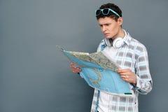 Homem isolado na posição cinzenta do conceito do turismo da parede que olha o mapa referido imagem de stock
