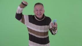 Homem japonês maduro feliz que usa o telefone e obtendo a boa notícia video estoque