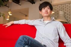 Homem japonês que relaxa no sofá vermelho, televisão de observação na sala de visitas imagem de stock royalty free