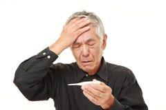 Homem japonês superior com febre Foto de Stock Royalty Free