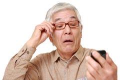 Homem japonês superior com presbyopia Fotografia de Stock Royalty Free