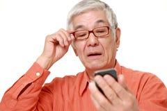 Homem japonês superior com presbyopia Fotografia de Stock