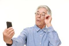 Homem japonês superior com presbyopia Foto de Stock Royalty Free