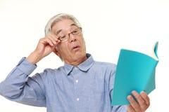 Homem japonês superior com presbyopia Imagem de Stock
