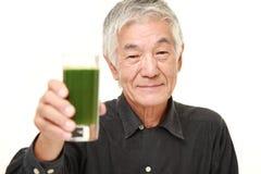 Homem japonês superior com suco vegetal verde Fotografia de Stock Royalty Free