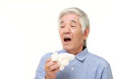 Homem japonês superior com uma alergia que espirra no tecido Imagens de Stock Royalty Free