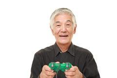 Homem japonês superior que aprecia um jogo de vídeo Fotografia de Stock Royalty Free