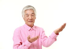 Homem japonês superior que apresenta e que mostra algo Foto de Stock