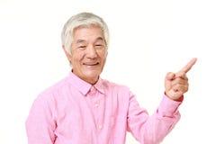 Homem japonês superior que apresenta e que mostra algo Imagem de Stock
