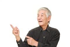 Homem japonês superior que apresenta e que mostra algo Fotografia de Stock Royalty Free