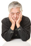 Homem japonês superior que dorme na tabela Imagem de Stock
