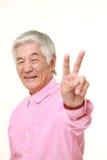 Homem japonês superior que mostra um sinal da vitória Imagem de Stock