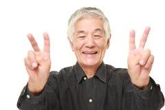 Homem japonês superior que mostra um sinal da vitória Fotografia de Stock Royalty Free