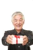 Homem japonês superior que oferece um presente Fotografia de Stock