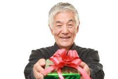 Homem japonês superior que oferece um presente Foto de Stock Royalty Free