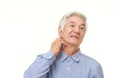 Homem japonês superior que risca seu pescoço Imagem de Stock