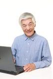 Homem japonês superior que usa o laptop Fotografia de Stock Royalty Free