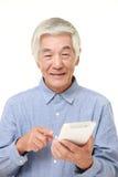 Homem japonês superior que usa o tablet pc Foto de Stock