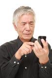 Homem japonês superior que usa o telefone esperto que olha confundido Imagens de Stock Royalty Free