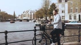 homem 4K europeu com bicicleta em uma ponte do rio Tipos masculinos à moda ocasionais no smartphone e olhares em torno de aprecia vídeos de arquivo