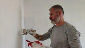 homem 4K farpado que pinta paredes interiores no plano usando a escova de pintura Homem novo considerável que faz reparos - pinta filme