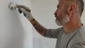 homem 4K farpado que pinta paredes interiores no plano usando a escova de pintura Homem novo considerável que faz reparos - pinta video estoque