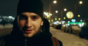 homem 4K novo em um chapéu negro que olha a câmera e o sorriso filme