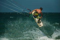 Homem Kitesurfing no mar azul Fotos de Stock