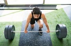 Homem latino-americano apto dos jovens no gym que levanta o barbell pesado imagem de stock