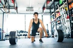 Homem latino-americano apto dos jovens no gym que levanta o barbell pesado imagens de stock royalty free
