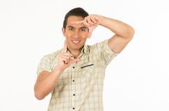 Homem latino-americano considerável novo que levanta fazendo um quadro Fotos de Stock Royalty Free